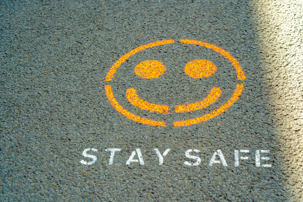 A smile spray painted onto the floor with stay safe written underneath